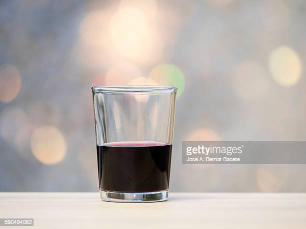 Glass of red wine on a wooden table with natural light