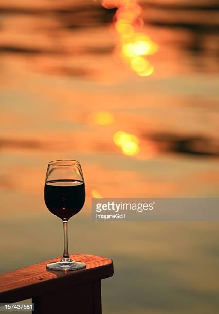 Verre de vin rouge sur une chaise de plage rustique