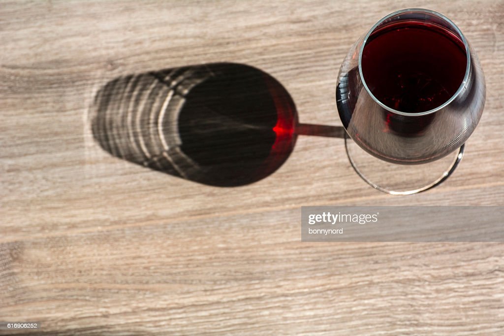 Glass of red wine on wooden background with shadow : Stock Photo