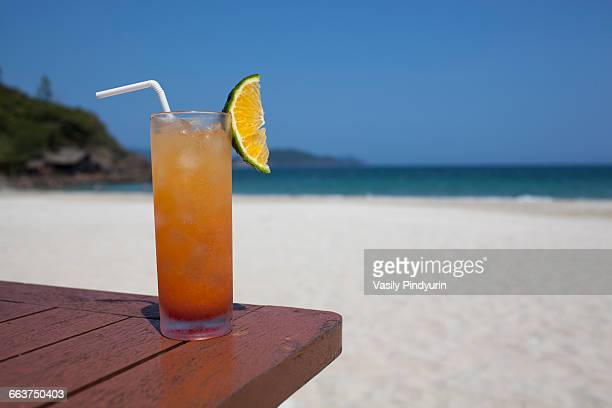 Glass of refreshment on wooden table at beach during sunny day