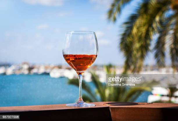 Glass of rose wine on balcony with summer port sea view