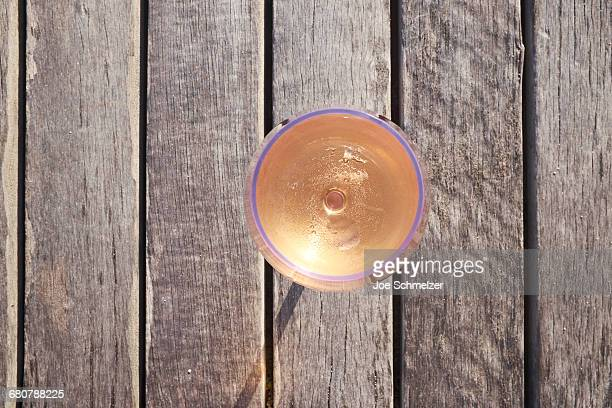 Glass of rose wine on wooden table