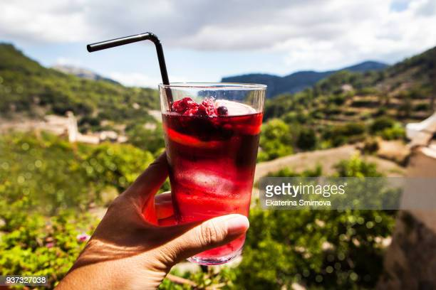 glass of sangria wine cocktail in woman hand - sangria stock pictures, royalty-free photos & images