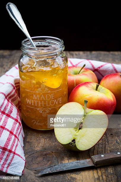 Glass of selfmade apple jam, dish towel and apples on wooden table