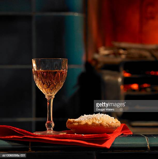 Glass of sherry and mince pie on napkin, fireplace in background