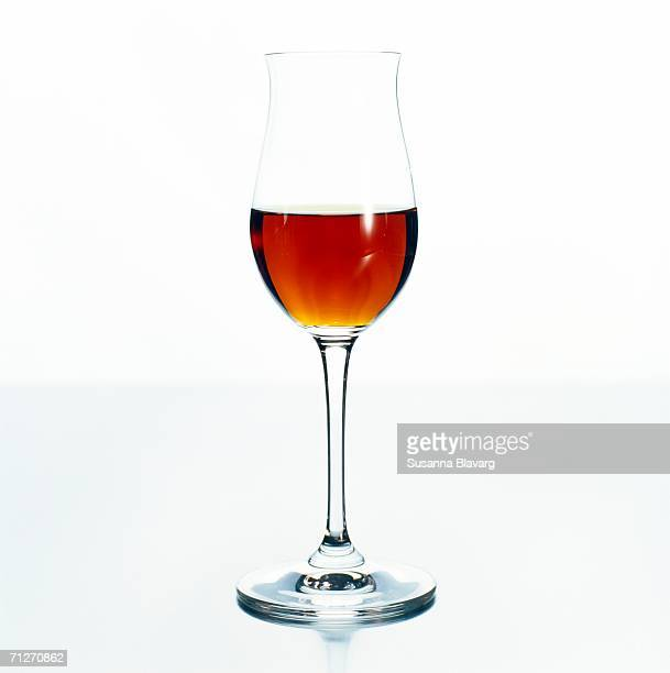 A glass of sherry on a white background, close-up.