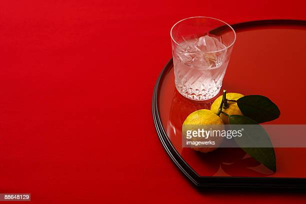 Glass of shochu with yuzu orange on tray, close-up