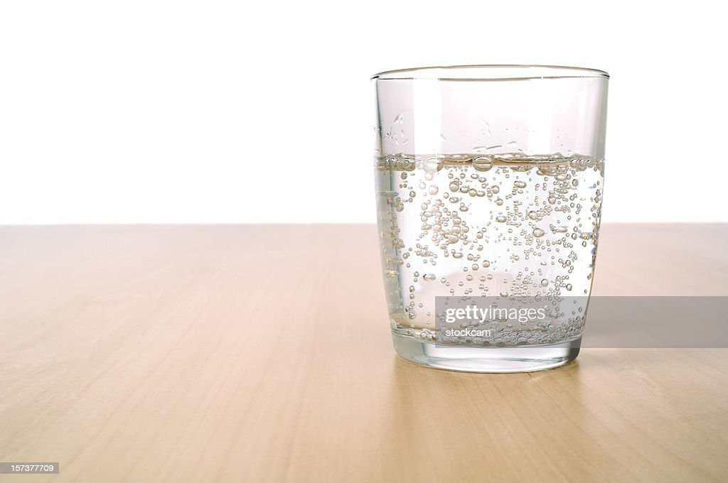 Glass of sparkling water on table : Stock Photo