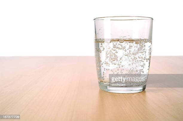 glass of sparkling water on table - carbonated water stock pictures, royalty-free photos & images