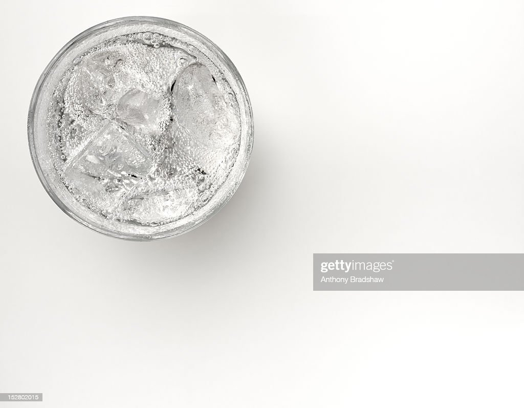 A glass of sparkling water with ice : Stock Photo