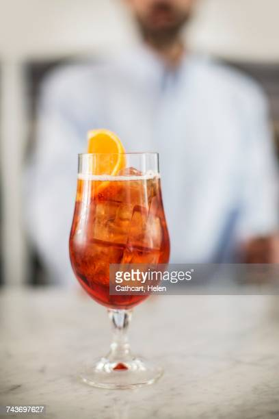 A glass of Aperol Spritz on a marble table