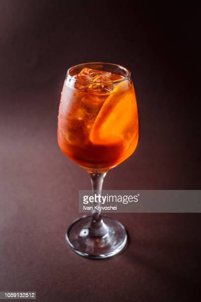 Glass of Aperol Spritz with orange on elegant dark brown background