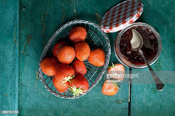 Glass of strawberry jam and strawberries in a wire basket