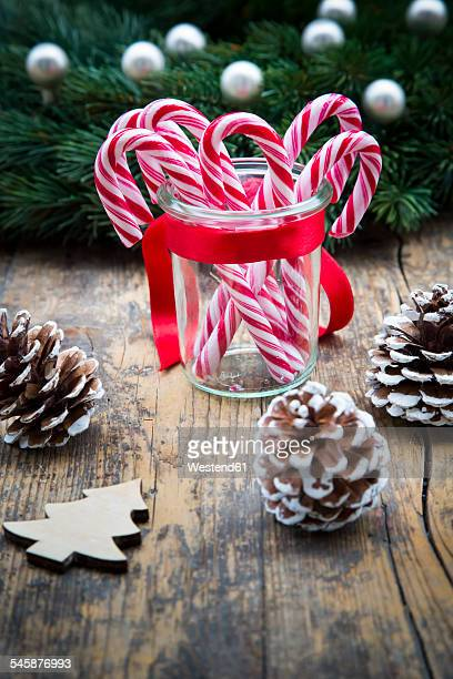 Glass of sugar canes and fir cones on wood