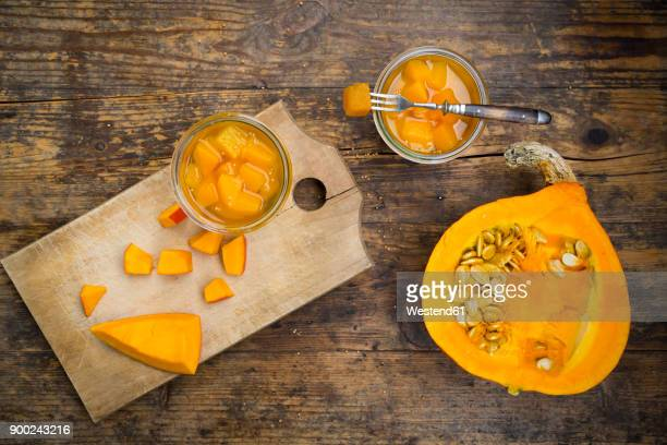 Glass of sweet-and-sour pickled pumpkin and raw pumpkin on wood