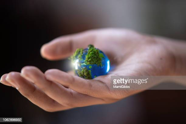 Glass of the earth's toys on the hand