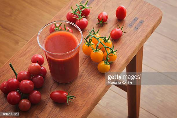 A glass of tomato juice and newly picked tomatoes