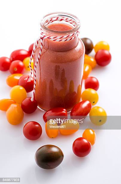 Glass of tomato smoothie and different tomatoes on white ground