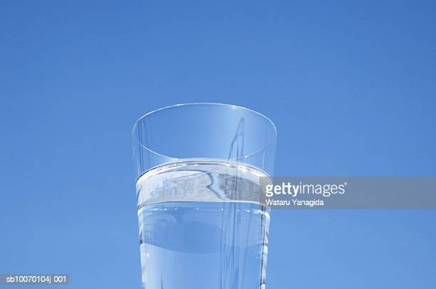 Glass of water against sky
