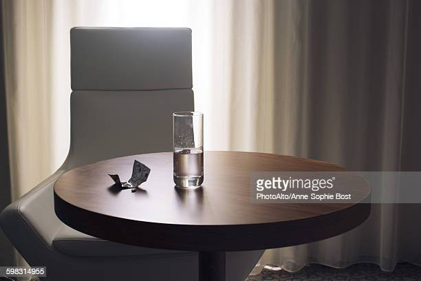 Glass of water and medication on table in hotel room