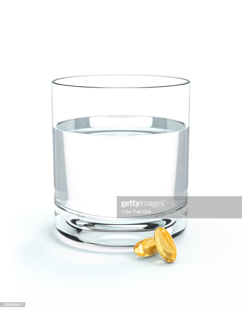 Glass of water and oil supplements : Stock Photo