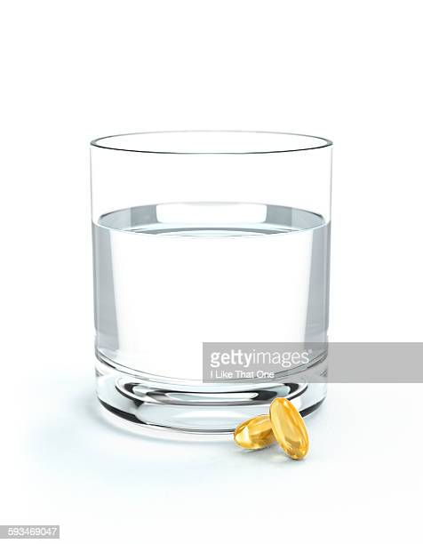 glass of water and oil supplements - atomic imagery stock pictures, royalty-free photos & images