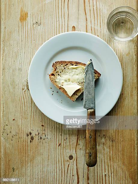 Glass of water and plate with bread and butter