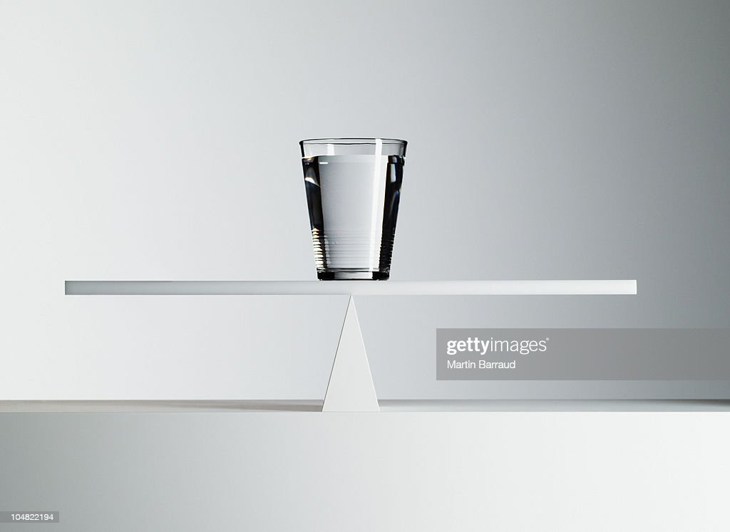 Glass of water balancing on middle of seesaw : Stock Photo