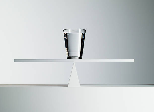 glass of water balancing on middle of seesaw - 平衡 個照片及圖片檔