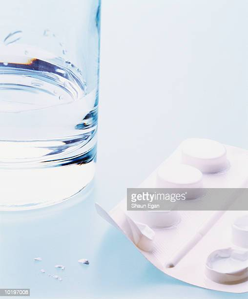 Glass of water beside pack of pills, close-up