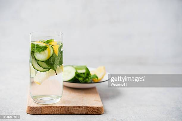 Glass of water flavoured with cucumber, lemon and mint