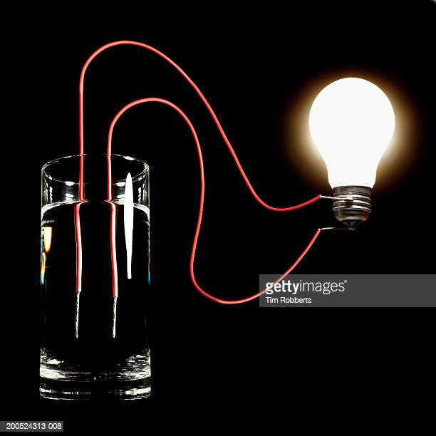 Glass of water hooked up to light bulb, black background