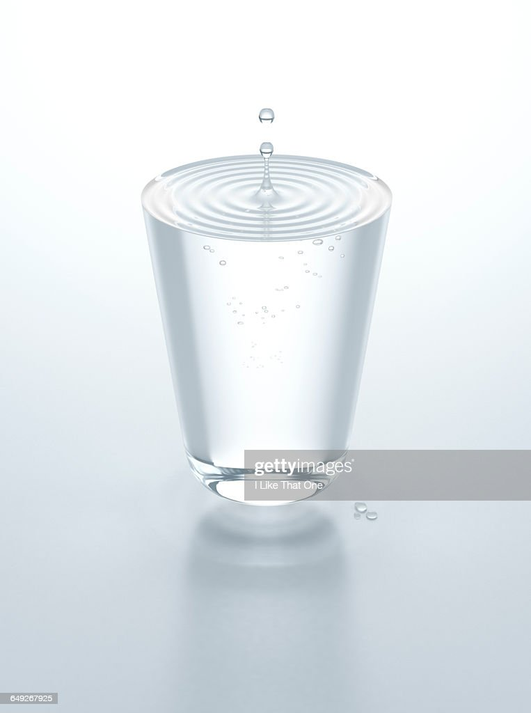 Glass of water hovering above table : Stock Photo