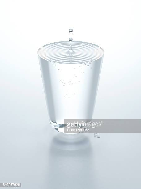 Glass of water hovering above table