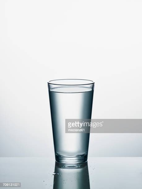 Glass of water in front of white background