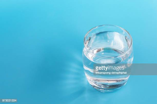 a glass of water on a blue background. - glass of water stock pictures, royalty-free photos & images