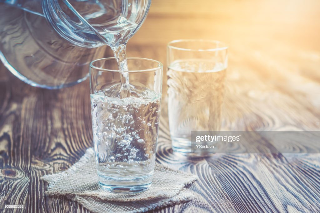 Glass of water on a wooden table : Stock Photo