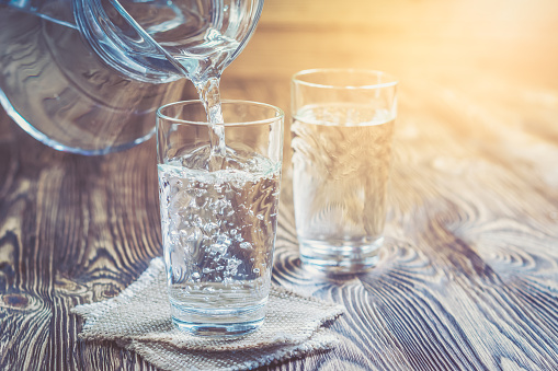 Glass of water on a wooden table 908985588