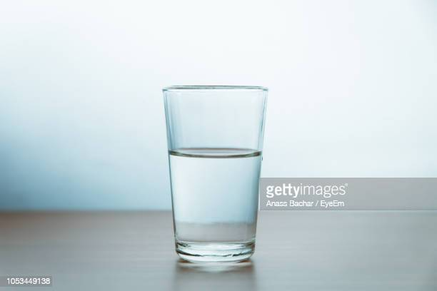 glass of water on table against wall - drinking glass stock pictures, royalty-free photos & images