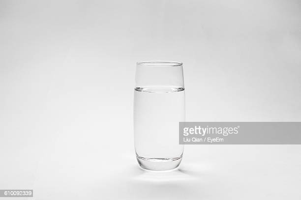 glass of water on table against white background - drinking glass stock pictures, royalty-free photos & images