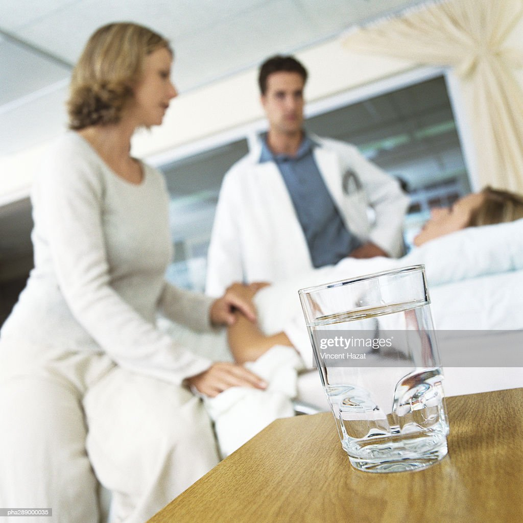 Glass of water on table and patient receiving visit from male doctor and woman : Stockfoto