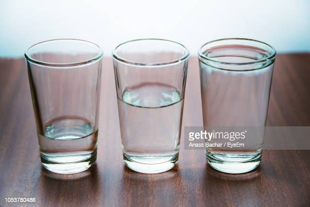 Glass Of Water On Wooden Table Against Wall