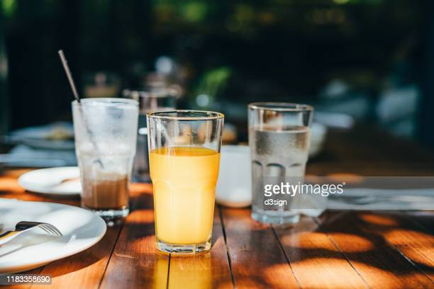 a glass of water, orange juice and coffee served on table in an outdoor restaurant against beautiful sunlight - juice drink stock pictures, royalty-free photos & images