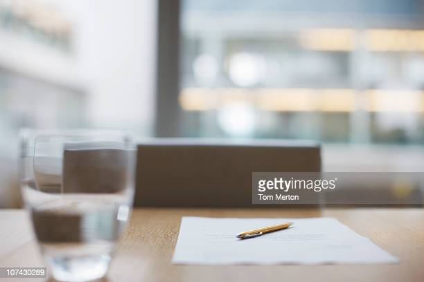 Glass of water, paper and pen on conference room table