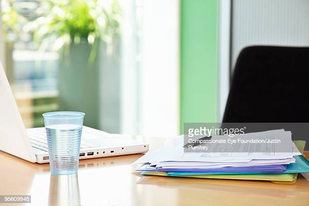 """glass of water, paperwork and computer on a desk - """"compassionate eye"""" fotografías e imágenes de stock"""