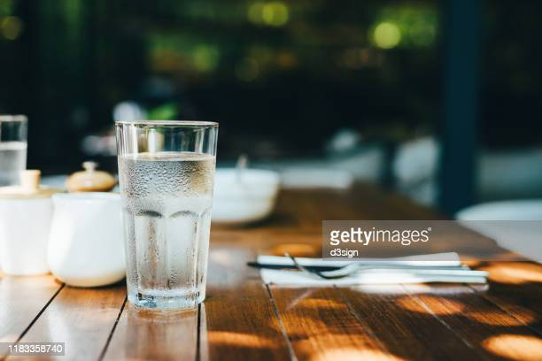 a glass of water served on table in an outdoor restaurant against beautiful sunlight - drinking glass stock pictures, royalty-free photos & images