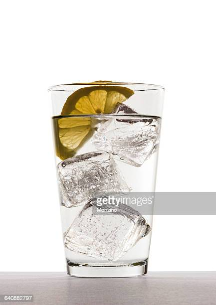 Glass of water with ice cubes and lemon slice