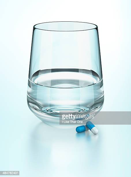 glass of water with two medication capsules - atomic imagery stock pictures, royalty-free photos & images