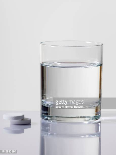 Glass of water with two pills effervescent paracetamol for pain