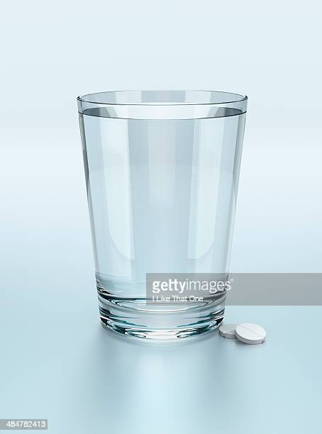 glass of water with two tablets - atomic imagery stock pictures, royalty-free photos & images